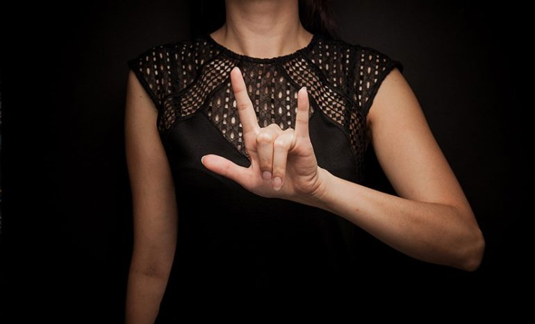 Against a black background, we see a woman wearing a black dress as she signs LOVE.